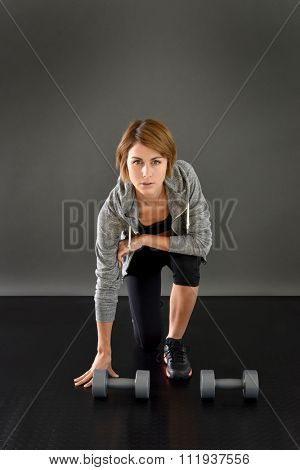 Fitness girl knelt on floor lifting dumbbells, isolated