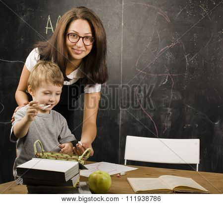 little cute boy in glasses with young real teacher, classroom studying at blackboard