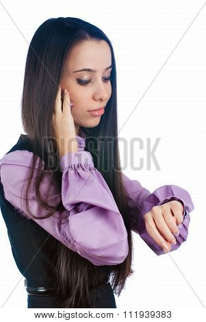 Attractive woman talks on phone and looks on watch