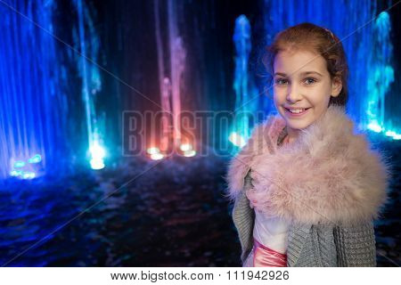 Little cute girl in knit fur jacket is standing near colored fountain.