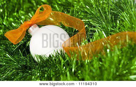 White Christmas ball with orange ribbon