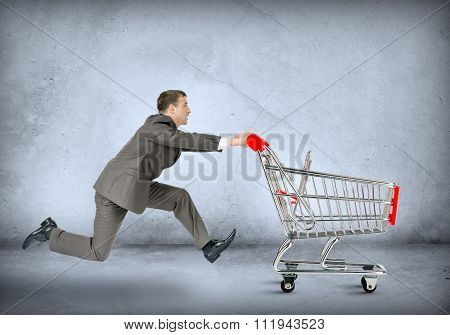 Businessman pushing empty shopping cart
