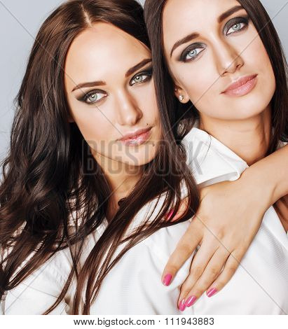two sisters twins posing, making photo selfie, dressed same white shirt, diverse hairstyle friends s
