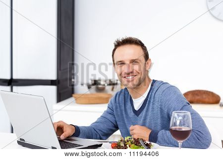Happy Man Looking At His Laptop While Eating A Salad