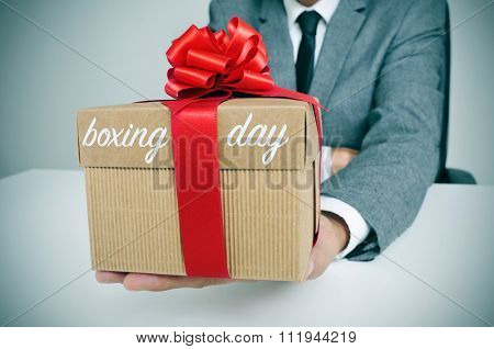 a young caucasian man in suit sitting at his office holding a gift tied with a red ribbon and the text boxing day