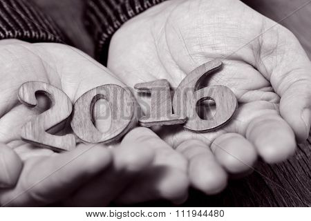 closeup of wooden numbers forming the number 2016, as the new year, in the hands of a man, in black and white