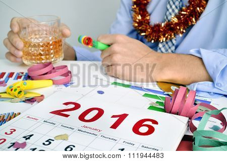 a young caucasian businessman drinking in the office during or after a new years party, with a 2016 calendar, party horns, streamers and confetti in his desk