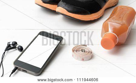 running shoes orange juice measuring tape and phone on white wood background