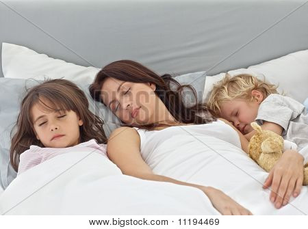 Adorable Children Sleeping With Their Mother On Her Bed