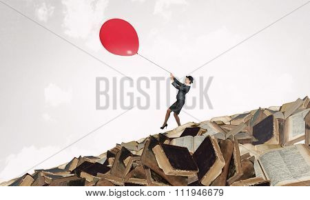 Businesswoman in suit and bowler hat flying on balloon