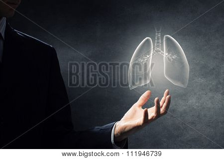 Male hand on dark background holding lungs symbol