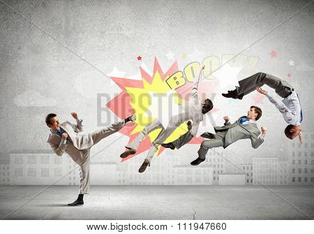 Young determined karate businessman fighting with team of businesspeople