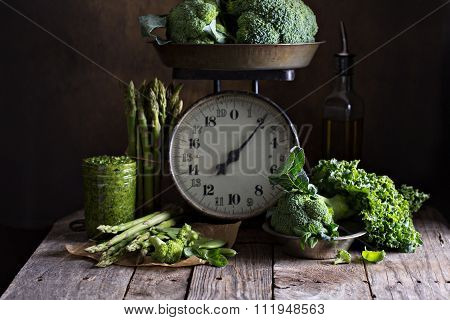 Fresh green vegetables on old kitchen scales