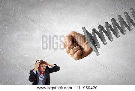 Young determined businessman fighting with human fist on spring