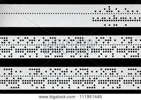 Closeup Of Perforated Punched Tape On Black Background