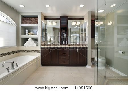 Master bath in luxury home with dark wood cabinetry
