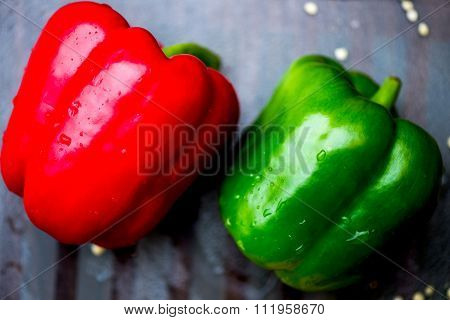 Red And Green Bell Peppers On The Chopping Board, Dark Background