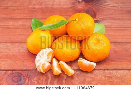 Several Mandarin Oranges On A Dark Wooden Surface