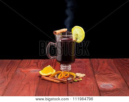 Mug Of Mulled Wine And Mulling Spices On Wooden Surface