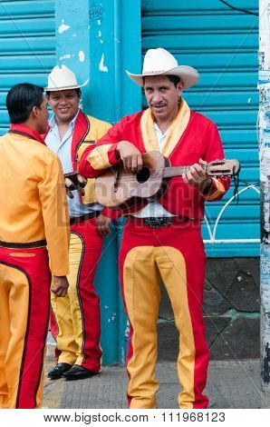 Men in red yellow Costumes and cowboy Hat Playing Guitar on street with blue background