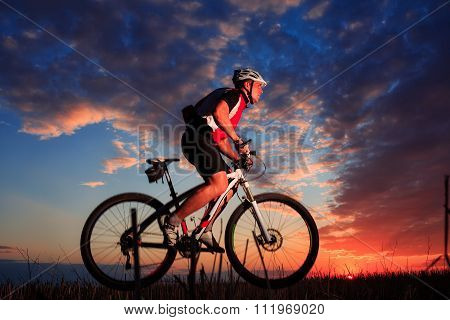 Man with bicycle at the sunset outdoor