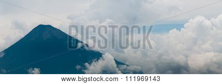 Big Summit of volcano Surrounded By Fog and thick Clouds over green field