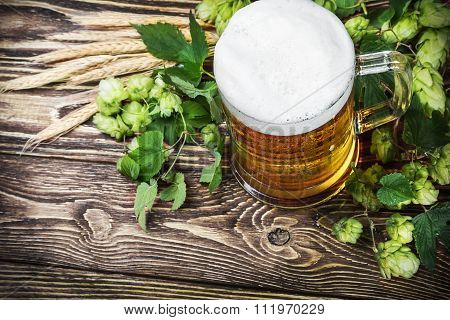 Mug With Beer With Hop On A Wooden Table