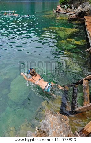 Woman swimming in very Clean and Clear lagoon lake Water next to a wooden path