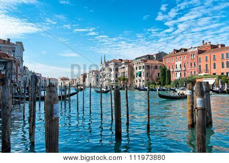 VENICE, ITALY - 17 OCTOBER 2015: Gondolas taking tourists for rides on the Grand Canal viewed between wooden mooring poles, Venice, Italy, in a travel concept. Venice, Italy on 17 October 2015.