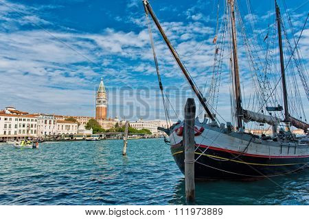 VENICE, ITALY - 17 OCTOBER 2015: Focus on Masted Boat in Foreground with View of San Giorgio Island and Monastery Bell Tower in Background on Grand Canal. Venice, Italy on 17 October 2015.