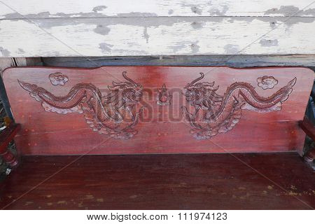 Red-brown wooden backrest background with sculpture of dragons and white wooden wall.