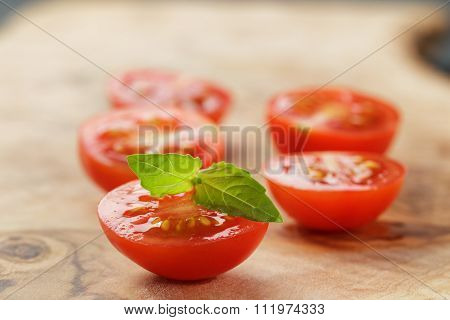 cut in half cherry tomatoes with basil leaf on wood table