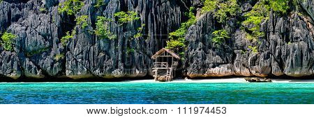 Lonely wooden bamboo house on stilts at a small hidden beach of rocky island