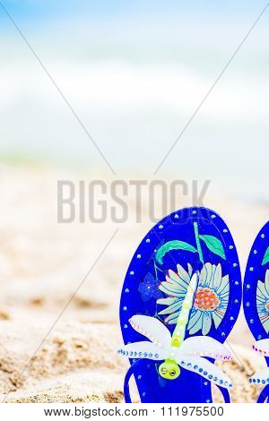 Blue Jelly Sandals With Dragonfly Laying On The Sand. Sea On The Background