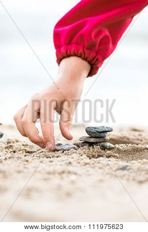Little Hand Placing Stone On The Pyramid On Sand. Sea In The Background