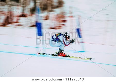downhill young girl athlete skiing to competition Russian Cup in alpine skiing. background blur effe