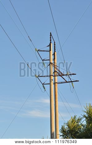 Two Concrete Support Power Line Against The Blue Sky