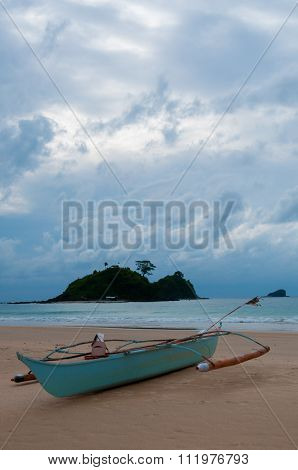 Blue Boat laying on the sand beach in front of ocean and island