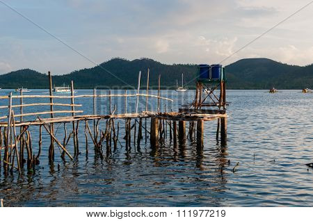 Small wood jetty in front of ocean and island