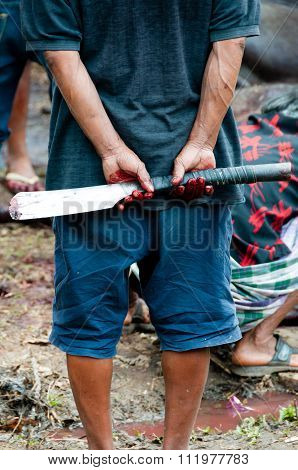 Man Holding a Butcher Knife behind his back