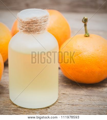 Tangerine Oil In A Glass Bottle With Fresh Tangerines On Wooden Background