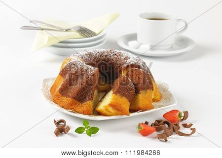sliced marble bundt cake and cup of coffee on white background