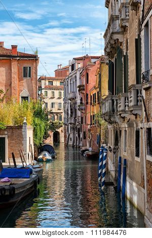 Picturesque small back canal in Venice, Italy with colorful traditional striped mooring poles and moored boats between historical old buildings