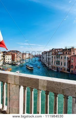 View from a stone balcony of the Grand Canal and its historic architecture with vaporetti and boat traffic, Venice, Italy