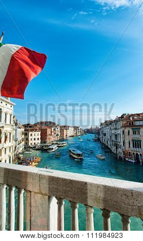 View from the balcony of Ca Foscari of the Grand Canal with vaporetto boat traffic and historical palaces, Italian flag in the foreground on the balcony, Venice, Italy