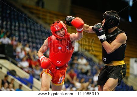 JAKARTA, INDONESIA - NOVEMBER 18, 2015: Seungmo Park of South Korea (red) fights Ji Fu Xu of China (black) in the men's 65kg Sanda final event at the 13th World Wushu Championship 2015.