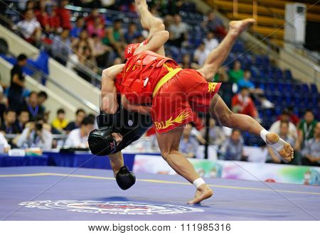 JAKARTA, INDONESIA - NOVEMBER 18, 2015: Mohsen Mohammadseifi of Iran (red) fights Ali Ay of Turkey (black) in the men's 70kg Sanda final event at the 13th World Wushu Championship 2015.