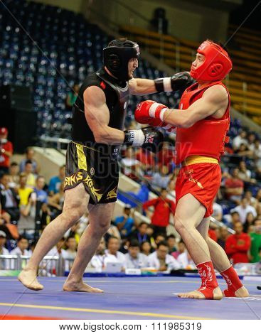 JAKARTA, INDONESIA - NOVEMBER 18, 2015: Gao Feng Fu of China (red) fights Muslim Salikhov of Russia (black) in the men's 80kg Sanda final event at the 13th World Wushu Championship 2015.