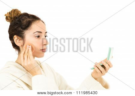 Woman Applying Make Up By Looking To Her Mirror