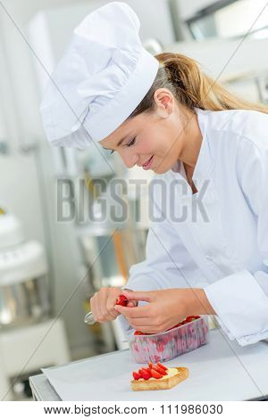 Chef cutting strawberries to decorate a tart